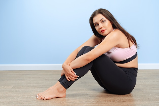 Fit woman in sportswear sitting on the floor in a gym