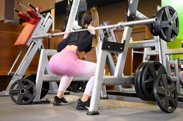 Fit woman squats with barbell back in front of mirror inside gym