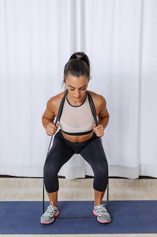 Fit woman squatting with resistance band