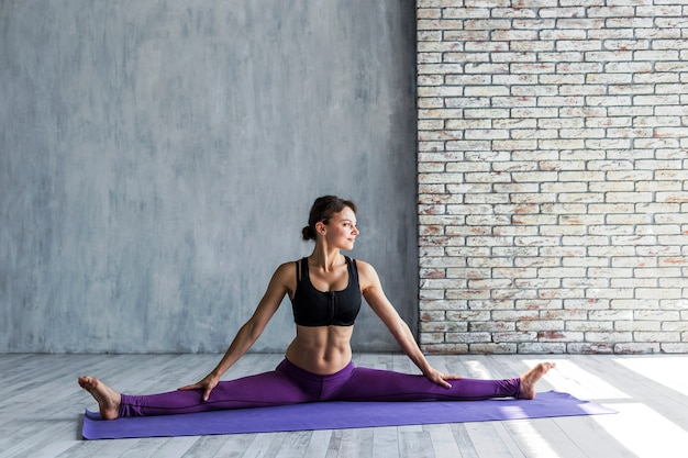 Fit woman standing in a split position