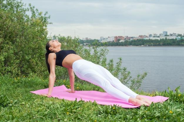 屋外の芝生公園で逆板張り運動を行う上向き板ポーズで体を伸ばして女性に合います。