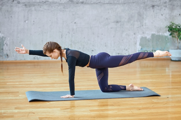 Fit woman stretching in hall.