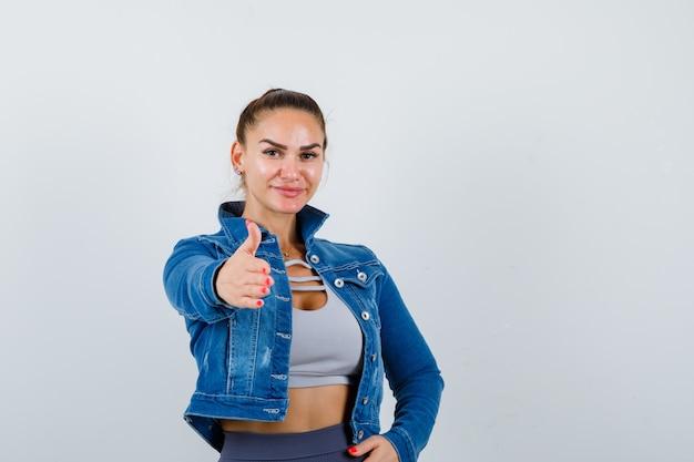 Donna in forma che allunga la mano verso la telecamera per salutare, con la mano sui fianchi in top corto, giacca di jeans, leggings e aspetto amabile. vista frontale.