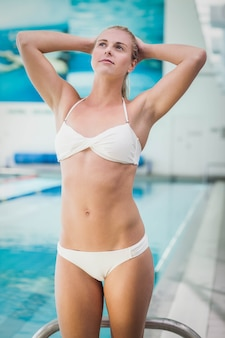 Fit woman stretching her arms at the pool