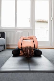 Подходит женщина, растягивая спину на коврике для йоги