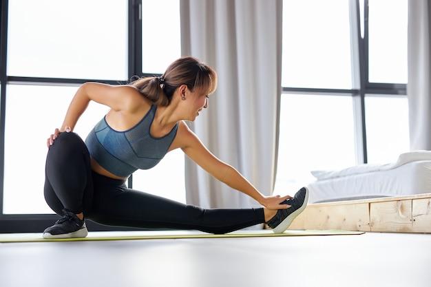 脚の筋肉を伸ばし、自宅でスポーツの柔軟性のエクササイズを行い、スポーツウェアを着用している女性にフィットします。女性は健康的なライフスタイルをリードします