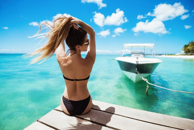 Fit woman stting on pier holding hair looking away