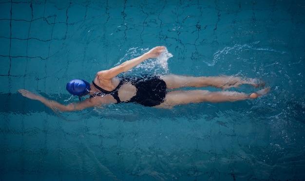 Подходящая женщина плавает в бассейне