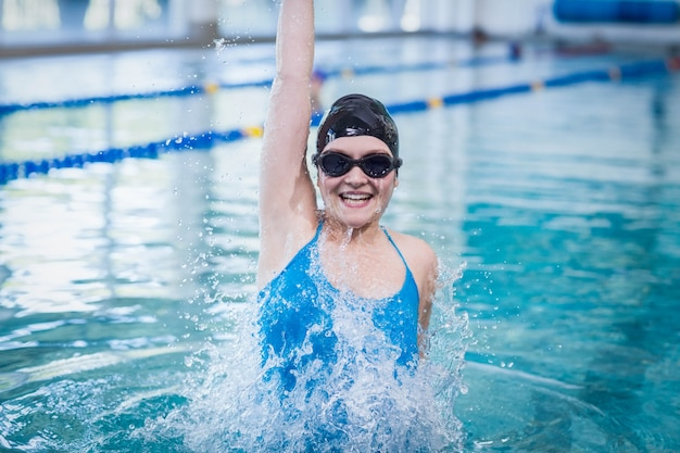 Fit woman triumphing with raised arm at the pool