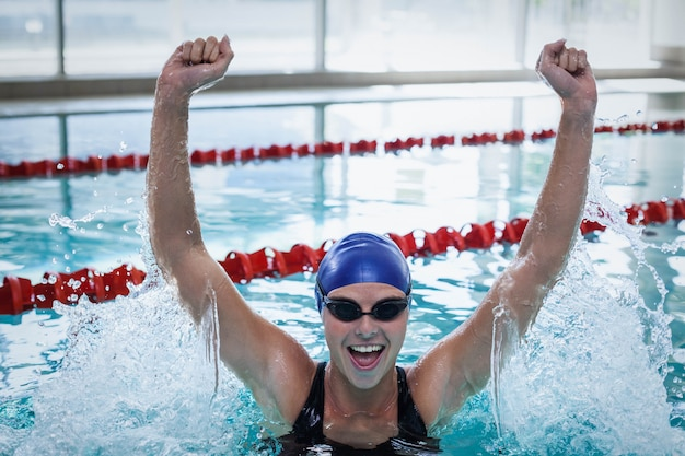 Fit woman triumphing with raised arms at the pool