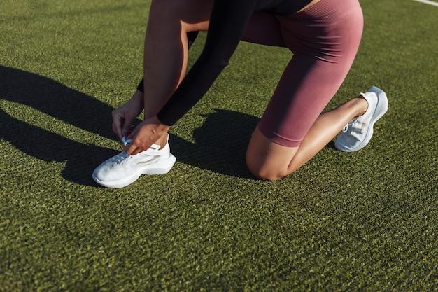 スタジアムで靴紐を結ぶ女性に合います。