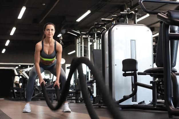 ジムでの筋力トレーニング中にバトルロープを使用して女性にフィットします。