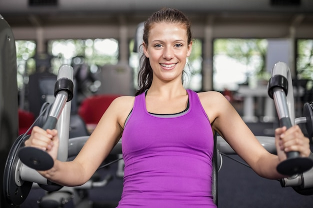 Fit woman using weight machine in gym