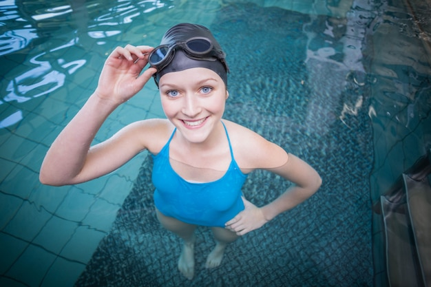 Fit woman wearing swim cap and goggles in the water at the pool