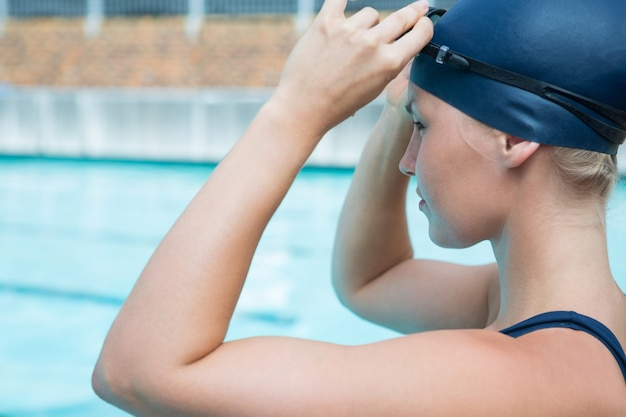 Fit woman wearing swimming goggle in pool