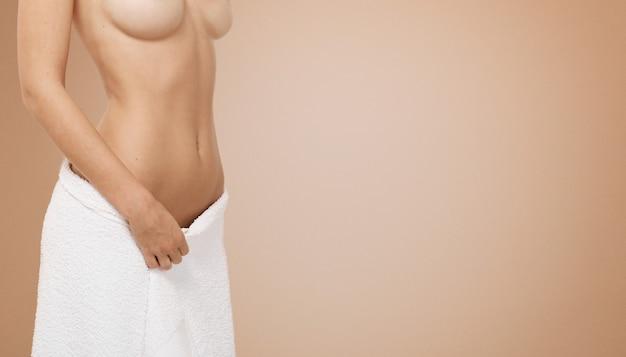 Подходит женщина в белом полотенце