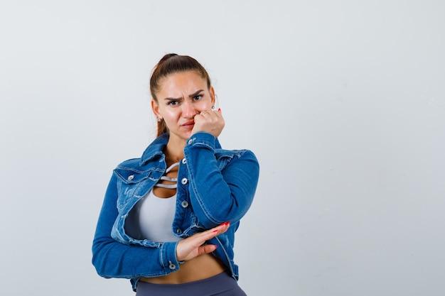 口の近くに拳を持ち、クロップトップ、ジーンズジャケット、レギンスに顔をゆがめ、心配そうに見える女性にフィットします。正面図。