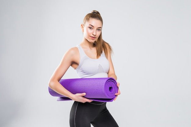 Fit woman with a gym mat isolated