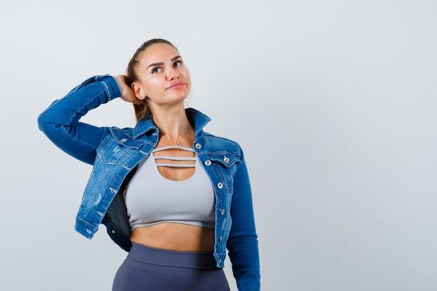 クロップトップ、ジーンズジャケット、レギンス、物思いにふける何かを考えて、頭に手を当てて女性にフィットします。正面図。