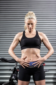 Fit woman with hands on abs at gym