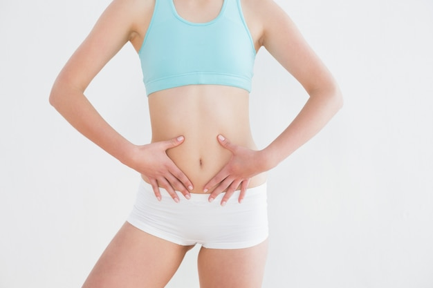 Fit woman with hands on belly against wall