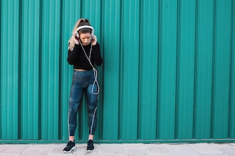 Fit woman with headphones on blue