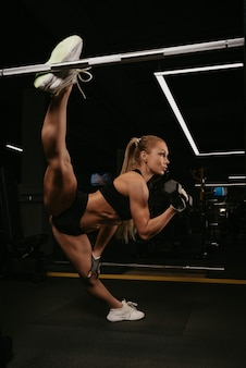 A fit woman with long blonde hair is doing a twine during dumbbell bicep curls in a gym. a girl is stretching.