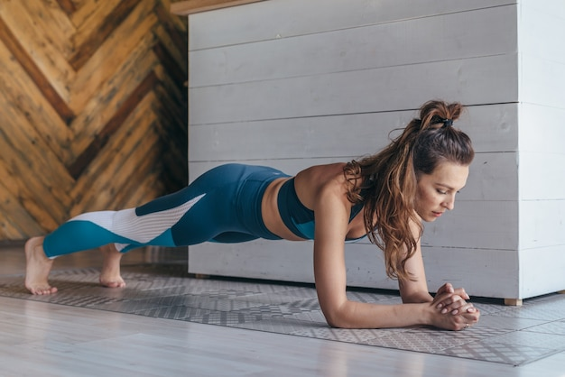 Fit woman working on abdominal muscles doing plank exercise, core workout at home.