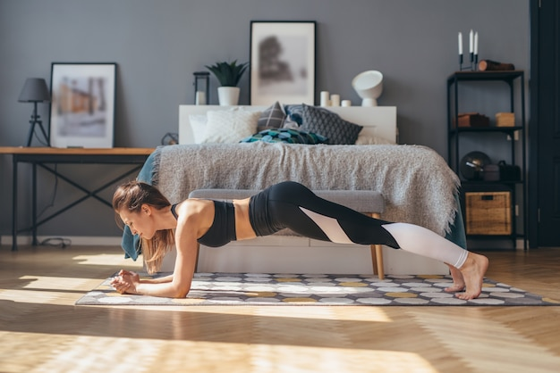 Fit woman working out doing forearm plank exercise at home in morning.