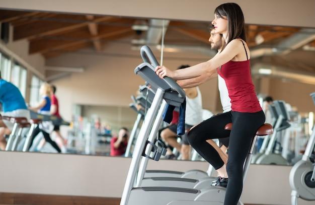 Подходит женщина, тренирующаяся в тренажерном зале на велотренажере