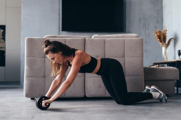 집에서 ab 운동 바퀴와 함께 운동을 맞는 여자.