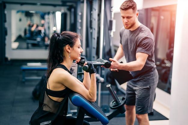 ジムでトレーナーと一緒に運動するフィット女性
