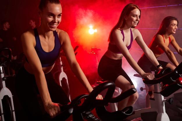 赤いネオンで照らされた煙のような空間で回転する自転車に乗っているジムで女性にフィットします。健康的なライフスタイルとスポーツの概念
