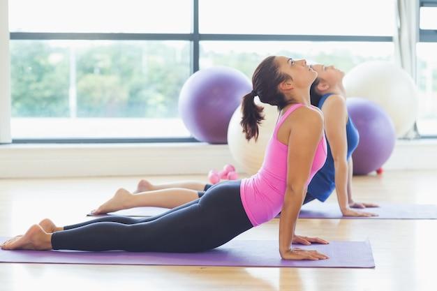 Fit women doing the cobra pose in fitness studio