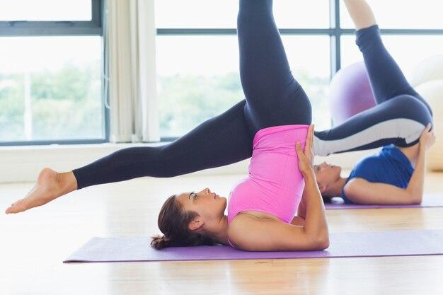 Подходящие женщины, занимающие позы в плечевой стойке в фитнес-студии