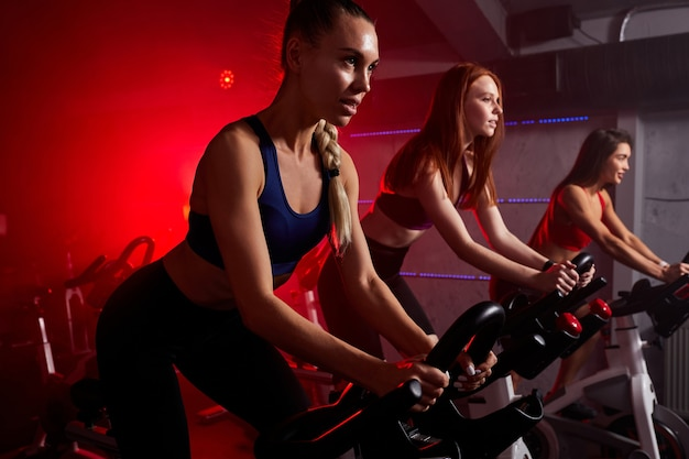 Fit women at the gym riding on spinning bike in red neon lighted smoky space. healthy lifestyle and sport concepts