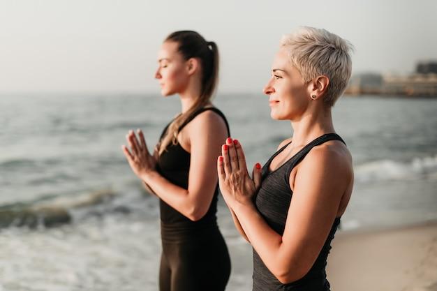 朝、海の近くで一緒に瞑想と祈りをする女性の母と娘にフィット