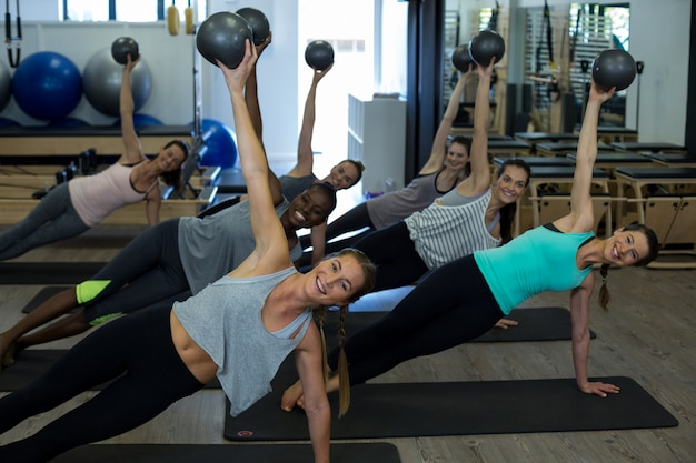 Подходящие женщины, выполняющие упражнения на растяжку с фитнес-мячом в тренажерном зале
