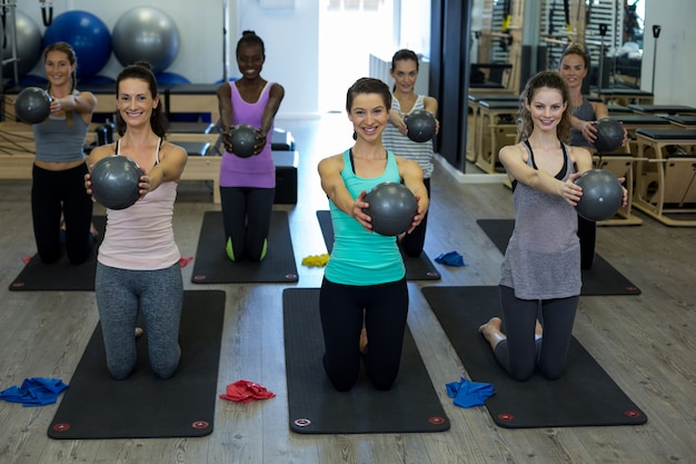 체육관에서 피트 니스 공으로 스트레칭 운동을 수행하는 맞는 여성