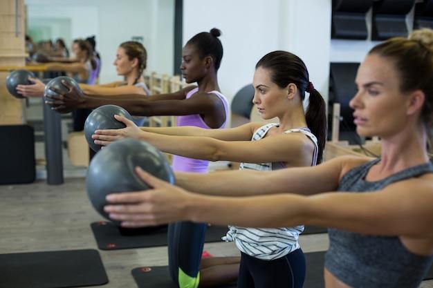 ジムでフィットネスボールでストレッチ運動を行う女性に適合