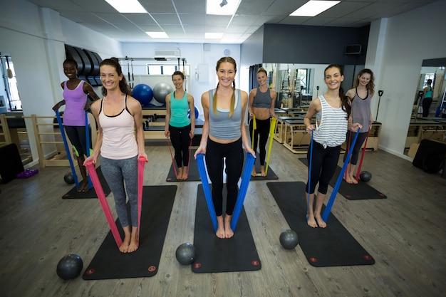 Подходящие женщины, выполняющие упражнения на растяжку с эспандером в тренажерном зале