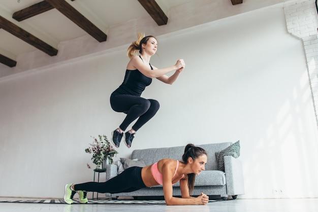 自宅でトレーニングをしている女性にぴったりです。女性が板の位置を実行している間、女の子は彼女の友人を飛び越えます。