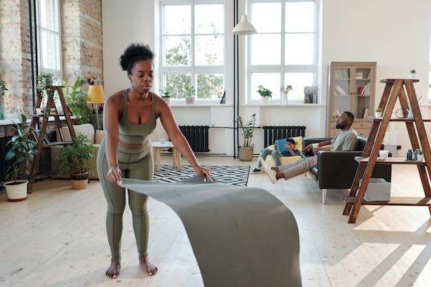 Подходит для молодой африканской женщины, которая кладет циновку на пол, собираясь тренироваться дома против своего мужа и маленького сына, отдыхающих на диване.