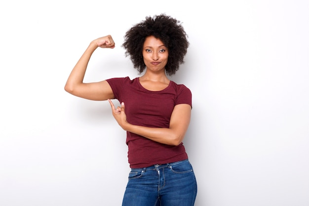 Fit young african woman pointing at arm muscles on white background