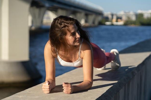 Подходит молодая спортивная женщина в розовых леггинсах, делая упражнения на планке, работая над мышцами живота и трицепсами на открытом воздухе. спортивная женская модель делает тренировку crossfit на набережной.