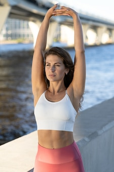 Fit young athletic woman stretching arms and shoulder joints on embankment. fitness female in pink leggings doing warmup workout outdoor.