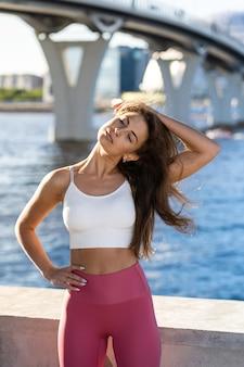 堤防で体を伸ばして若い運動女性に合います。ピンクのレギンスのフィットネス女性が首の筋肉を屋外でウォームアップします。