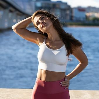 제방에 몸을 스트레칭 맞는 젊은 운동 여자. 야외 목 근육을위한 운동을 따뜻하게하고 핑크 레깅스 피트니스 여성.