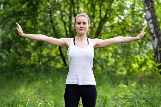 夏の日に公園で屋外で運動する白いトップと黒いスポーティなレギンスを身に着けている若い美しい女性に合います。