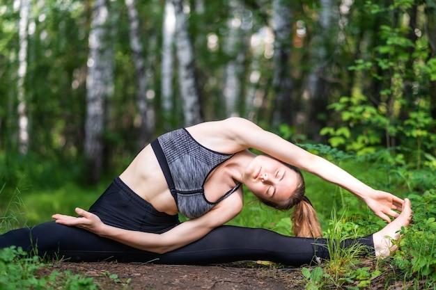 여름 날에 공원에서 야외에서 운동하는 흰색 상단과 검은 색 스포티 한 레깅스를 입고 젊은 아름 다운 여자를 맞습니다.